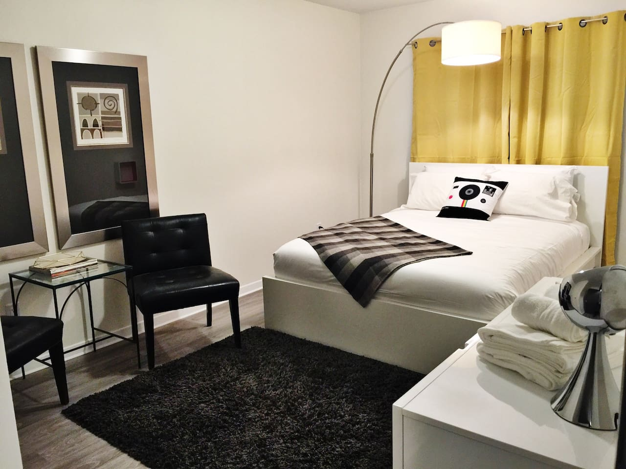 Bedroom #1 a spacious modern yet comfortable  room featuring a queen bed, 3 drawer dresser, closet, seating area, black-out blinds + quality linens. It is a cosy space perfect for 2 guests to call home.