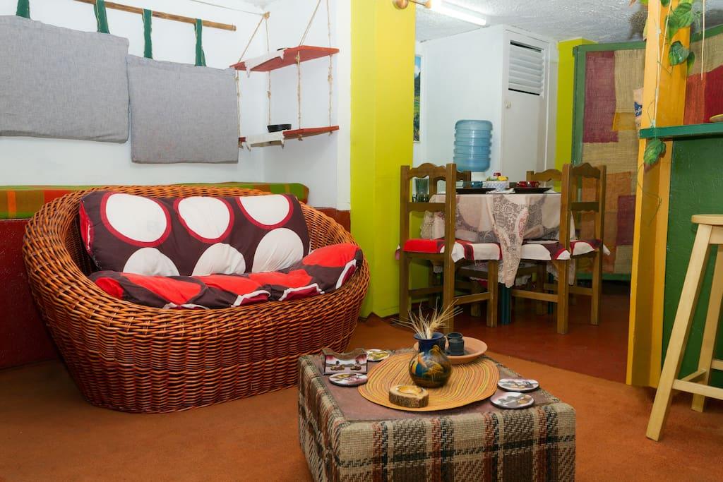 SOFÁ DE MIMBRE o ratán, mesa central, 3 repisas en madera y yute gruesos , los almohadones son elaborados en telar, les sostiene un bambú, los adornos son artísticos.El comedor para 4 personas. Se ve a la derecha parte de un taburete del  bar o desayunador