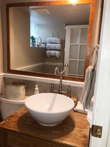 Bathroom with all amenities including: shampoo, conditioner, body wash, hairdryer and lots of towels
