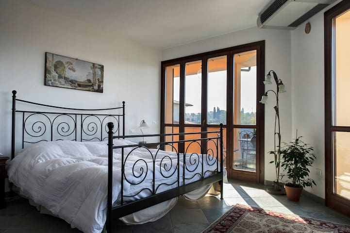 Master bedroom with king bed is sunny and open with wrap-around terraces.