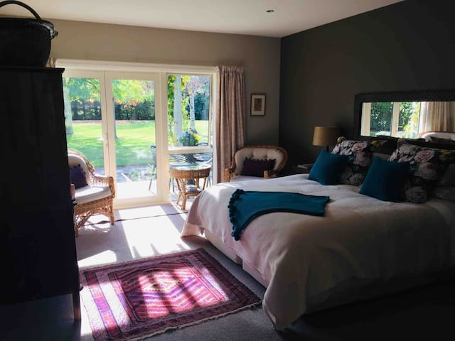 Main bedroom with french doors, views out to the private deck with hot tub and garden.