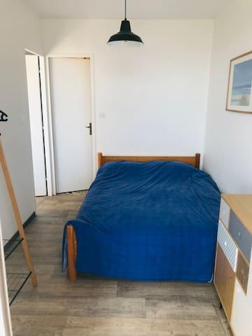 la chambre (lit 140) inclus : une commode et un portant avec des cintres la porte au fond est celle qui donne sur la SDB Dans le dos : porte fenêtre avec accès à la terrasse
