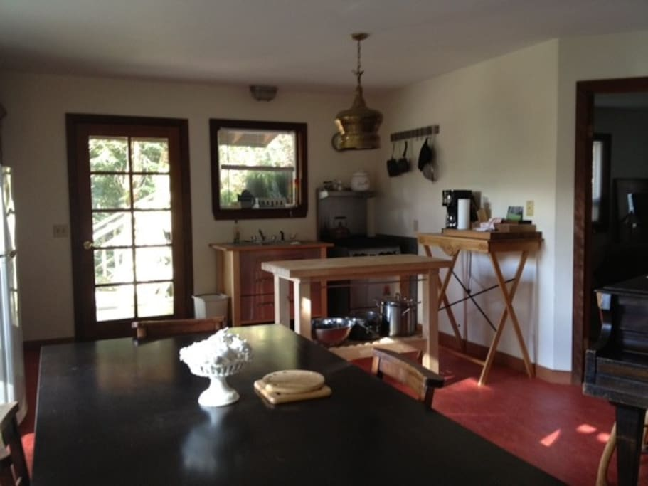 Looking back from the living room area you see the petite though well stocked kitchen. The old armoire is just off to the left of photo serving as the main cupboard with all the linens, cutlery and dishes you need. There is also a 4 burner wolf range it t