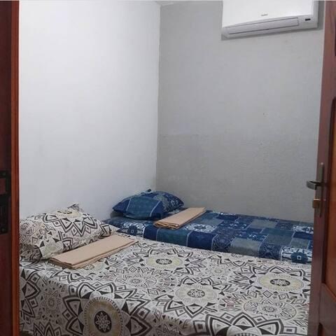 Quarto com duas camas de solteiro  com 04 camadas de roupas oferecidas pelo flat cada uma, ar condicionado, prateleiras, mesa de cabeceira e espelho.