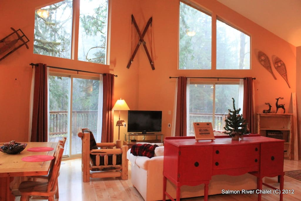 Spacious living room with vaulted ceilings and views of the forest.