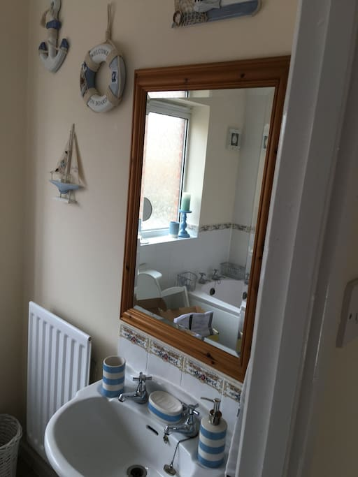 Bathroom with electric shower and full bath.