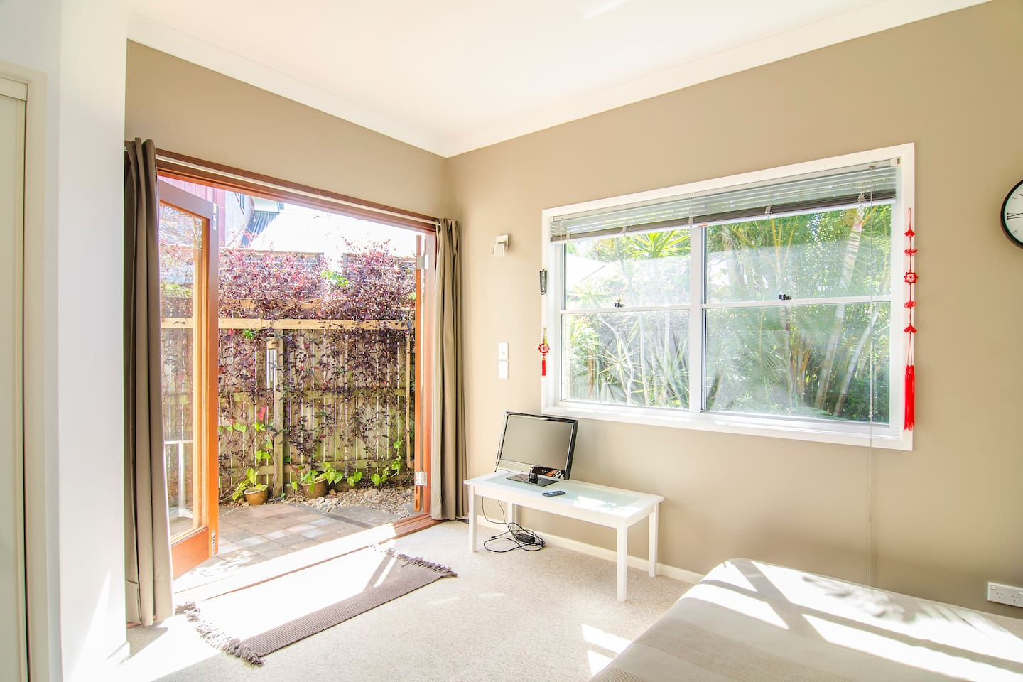 the flat studio is sunny and light and has three bifold doors leading into a private courtyard and windows to a subtropical garden. We change the colour scheme so some of the other pictures are the same studio. The queen bed has a low base.