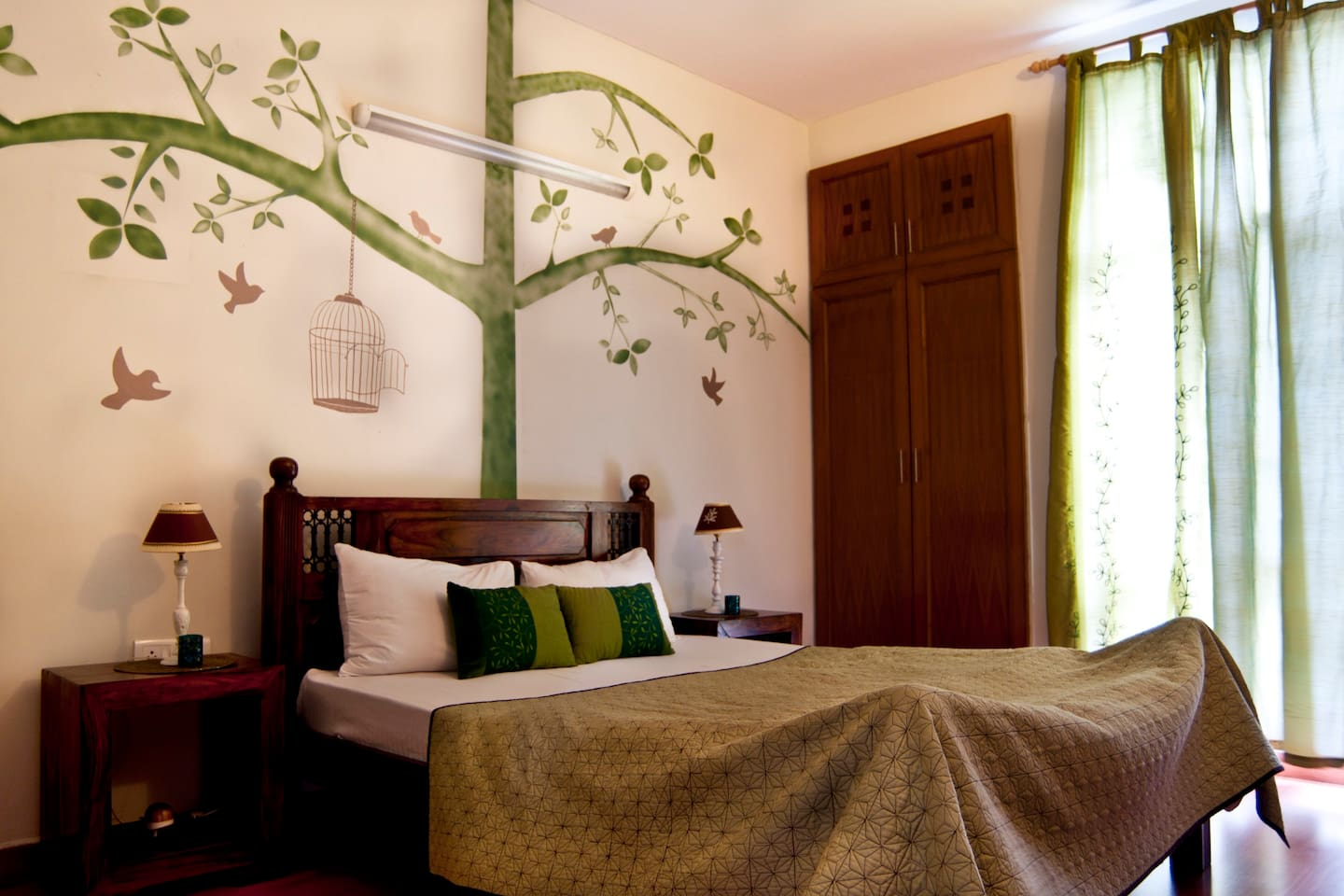 This is the Green Room with a beautiful hand painted motif in the background. It also has a small garden attached to it.