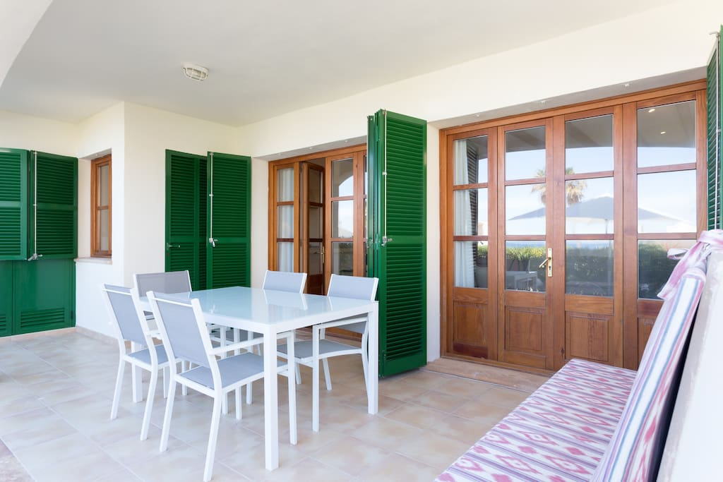 Shaded outdoor terrace space with access to kitchen and living area with dining table seating for up to 6 guests.