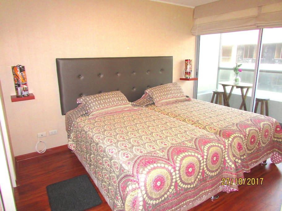 Dormitorio amplio con baño incorporado, walking closet y balcón con mesita y vista al mar.
