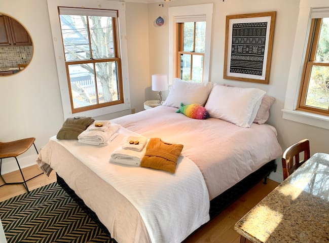 Primary bedroom: This bright bedroom has seasonal views of the harbor, a queen size bed, and a built-in desk and closet.