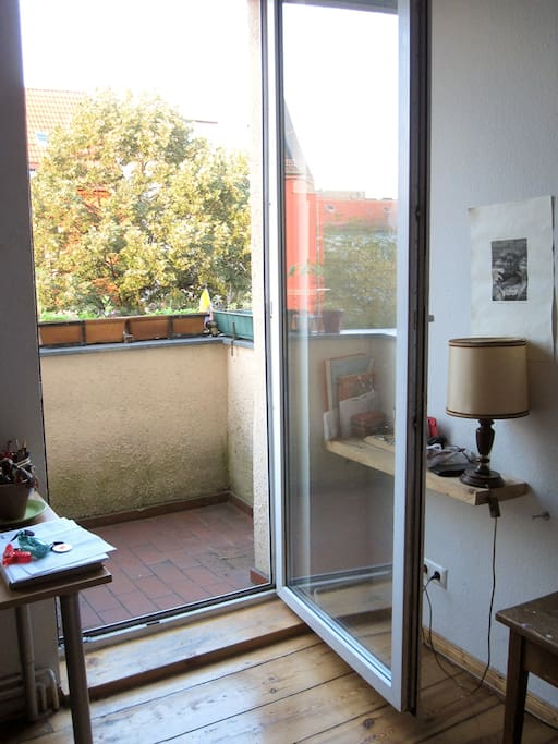 big room with bed, working place, couch and balcony