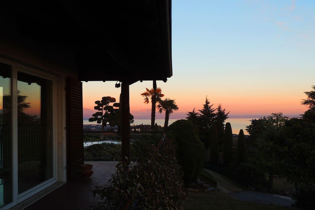 Un lato della casa  su cui corre il balcone con affaccio sul lago e sul giardino (al tramonto)