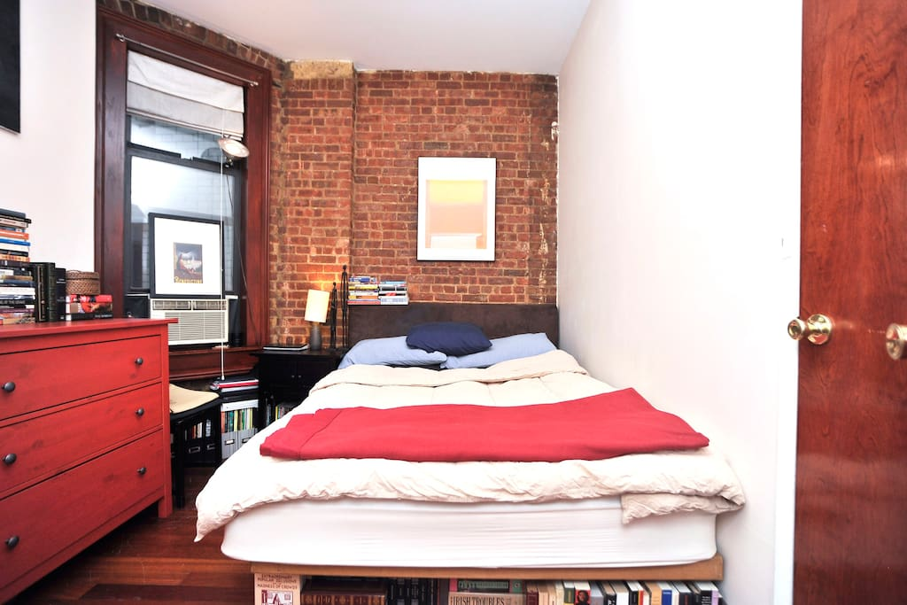 The room for rent! Has a closet, brick wall, hardwood floors, bed, matress and a comfy chair.