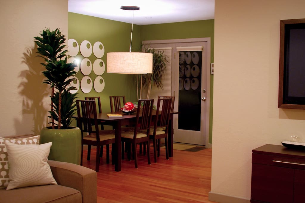 6 person dining table positioned between the living room and back patio door.