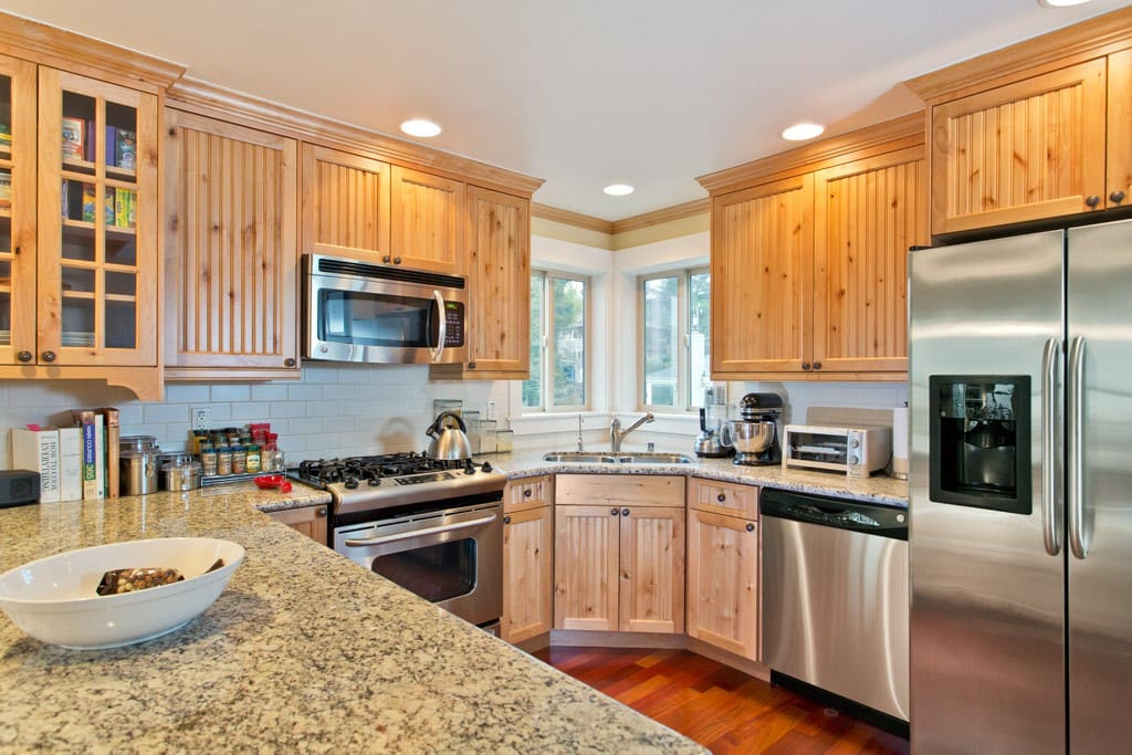 Open kitchen w/ granite counters, stainless appliances, and gas range