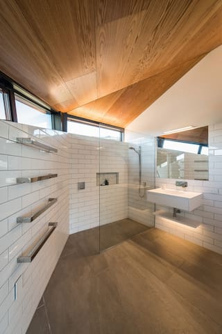 The master bedroom ensuite has a spacious shower, soaring ceilings and night lighting. The angled door is quirky. All three bathrooms have distinctive basins, subway tiles, mosaic shower inserts, designer chrome fittings and underfloor heating.