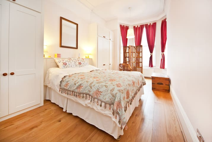 Double bedded bedroom with duvet and hanging cupboards with full length mirror, shelves and drawers for four people..