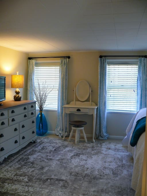 Master Bedroom vanity and full size dresser. Closet comes equipped with hangers, iron and ironing board. Master bedroom also has a TV with a Roku for streaming Direct TV Now and HBO.