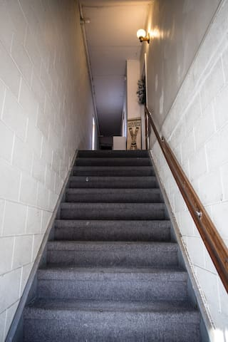 Head up the stairs. You're the door directly at the top. (There is a light switch at the bottom of the stairs and one inside the door).