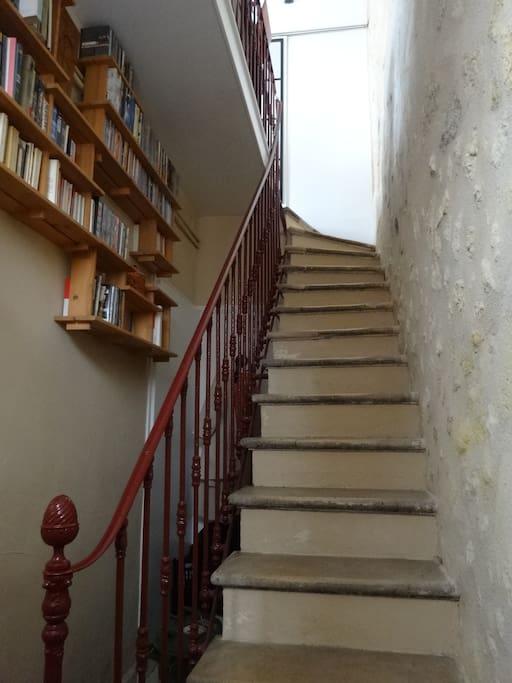 Entrée avec escalier et murs de pierre vers le 1er étage