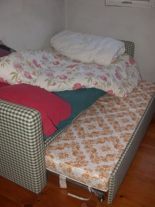 This trundle bed raises up on spring-loaded legs and creates a bed that is equal in height to the daybed.