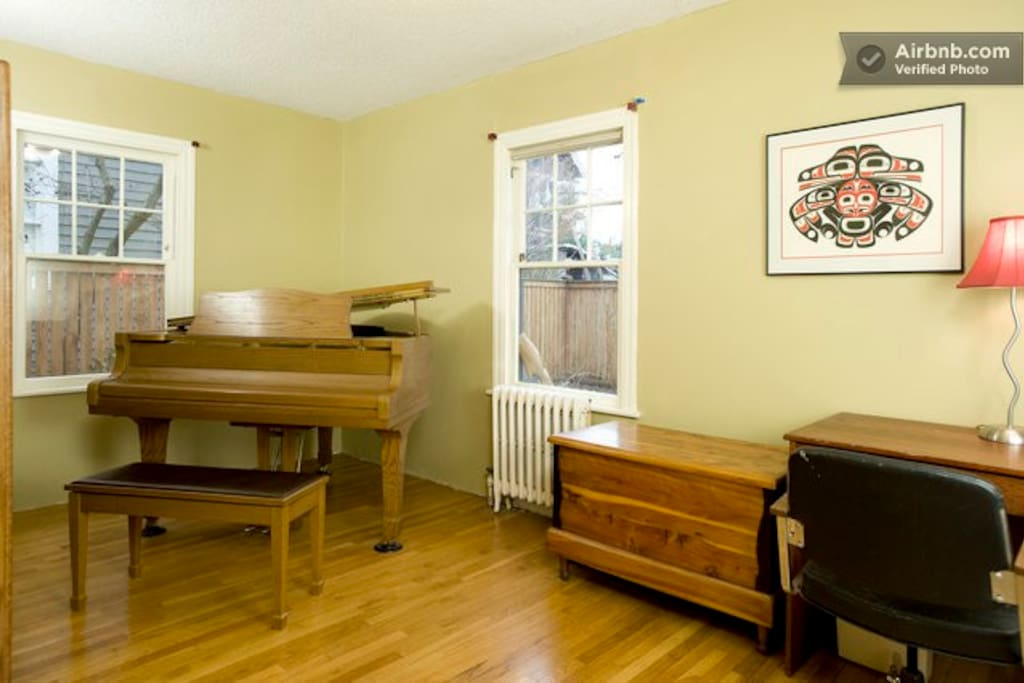 Spare room with a piano and desk for your use.