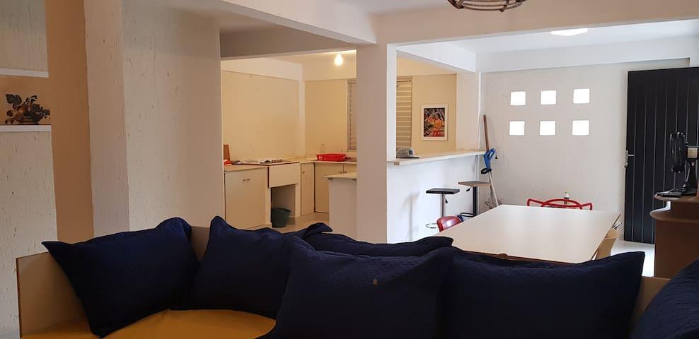 Sofás, mesa, cozinha integrada com bancada lanchonete.