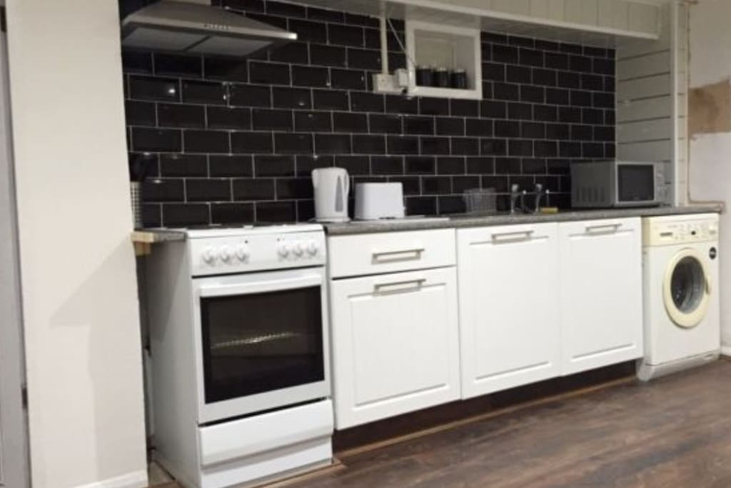 Kitchen with cooker ,fridge, washing machine, Microwave, kettle, toaster and pots and pans.