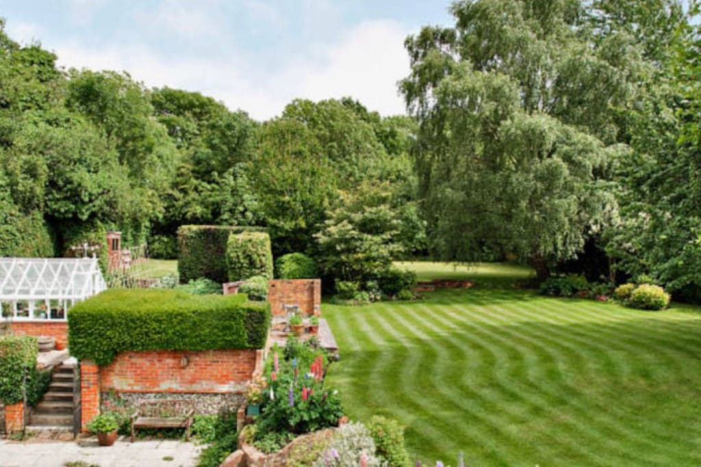 View of garden from house with top lawn football / games pitch visible at the back of the garden. Trampoline & paddling pool behind green house.