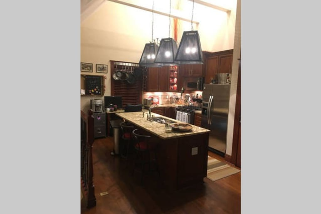 Kitchen with big island to dine at and dim-able lighting throughout.