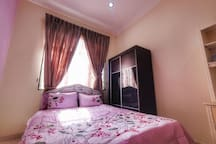 The 2nd room is furnished with a queen size bed, a cupboard, a dressing table and television