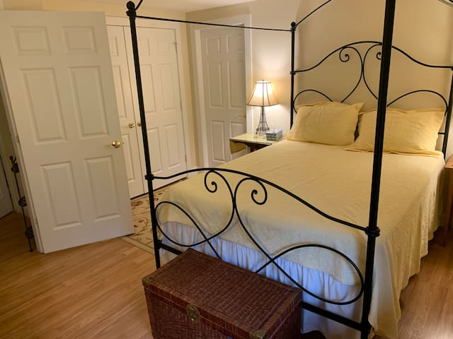 Wrought iron queen canopied bed with double closets.