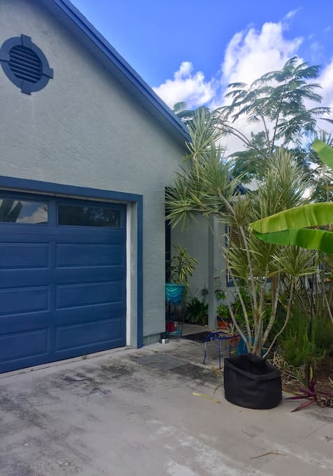 Front of home adorned with real plantings such as banana trees and fresh rosemary