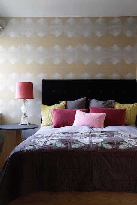 Hotel style bedroom with a 160 cm wide bed, yellow velvet curtains, blue velvet headboard and metallic tapestry