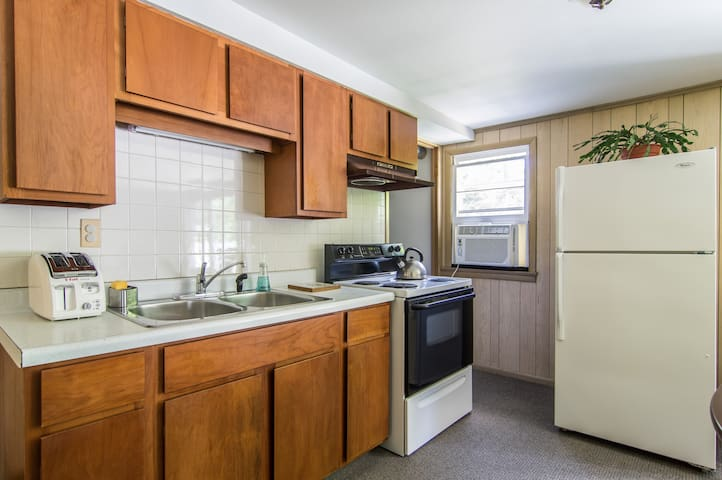 Full kitchen with stove, microwave and refrigerator
