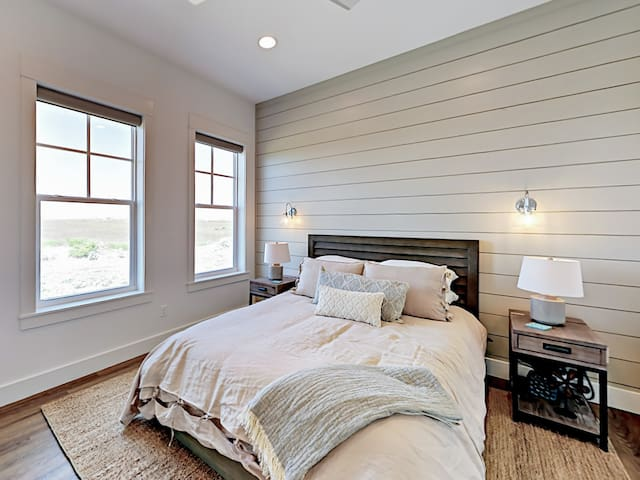Tasteful decor in the 2nd bedroom with queen bed and shiplap accent wall.
