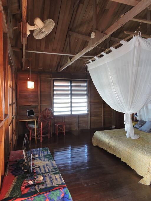 This is the largest guest room in the home and is situated on the front with a direct sea breeze most nights. There is NO AC in the room only fans and ocean breezes.