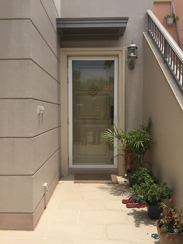 modern front entrance with greenery and lighting