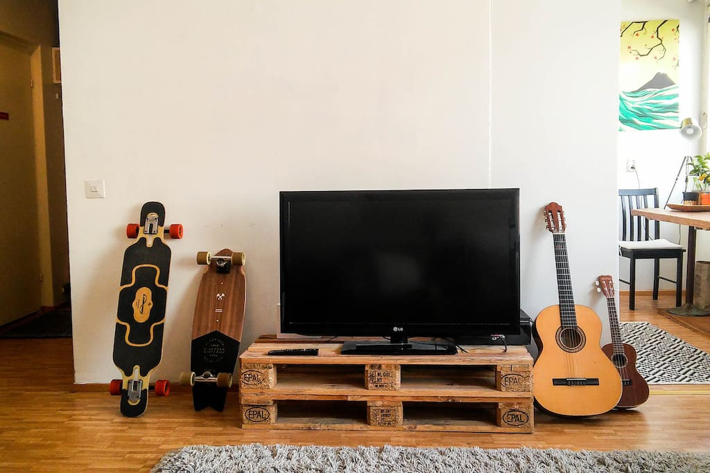 Flat-screen TV. We're most probably using the longboards ourselves but you can usually find the guitar and the uke here. Feel free to give them a play!