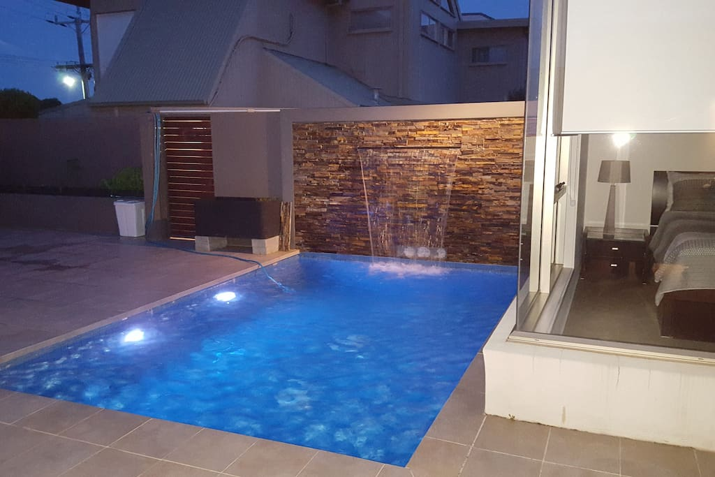 Night view of heated pool with waterfall