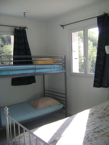 chambre avec deux lits simples et un lit double