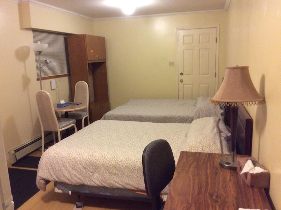 1 queen-sized and 1 double-sized bed with a table and a desk