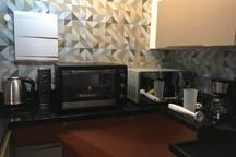 Cooktop de indução, forno elétrico, microondas, chaleira elétrica, cafeteria elétrica e mixer.