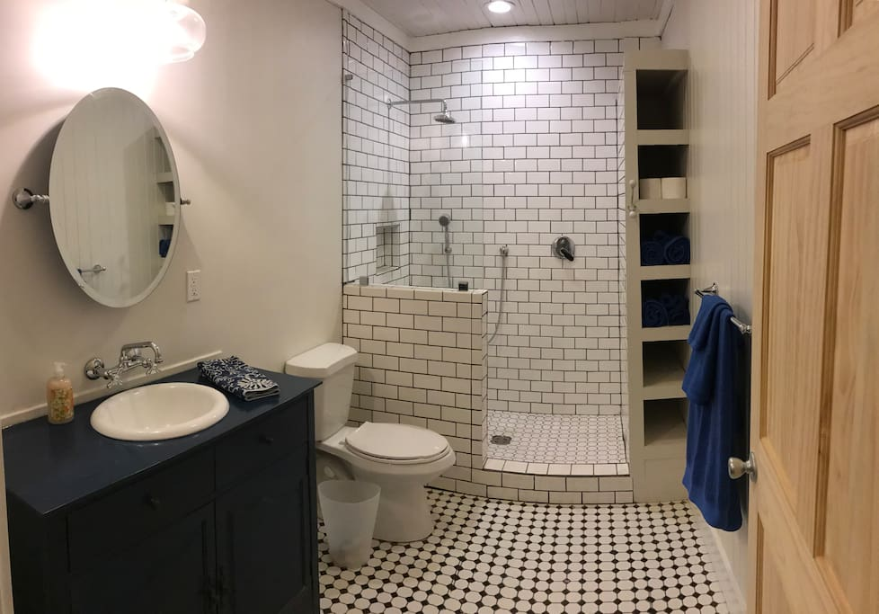 Hall bathroom has an open concept shower with subway tile, large vanity and tile floors.