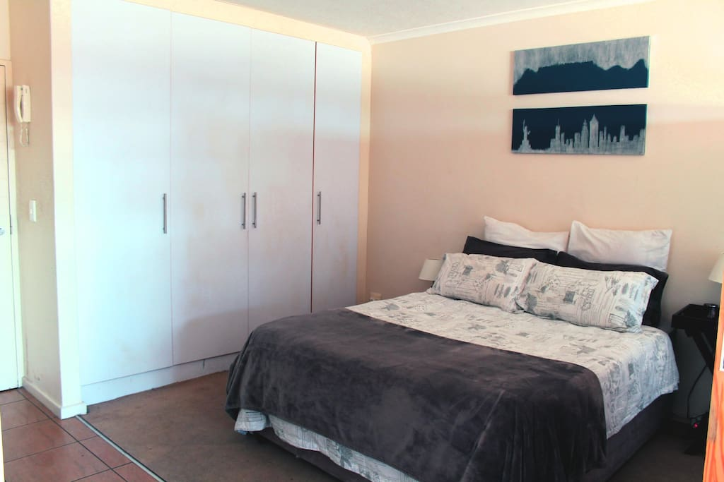 Bedroom area with ample cupboard space. Iron and ironing board located in cupboards.