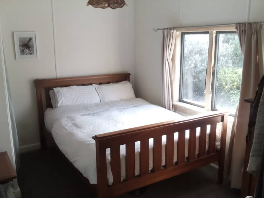 Queen size bed in Bedroom 1 with opening into lounge