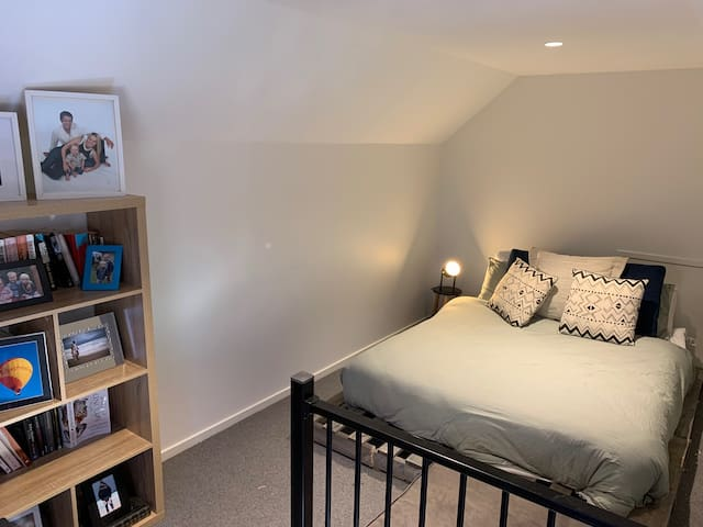 The loft bedroom has a queen bed on a pallet base. The loft is accessed by pull-down stairs in the lounge room.