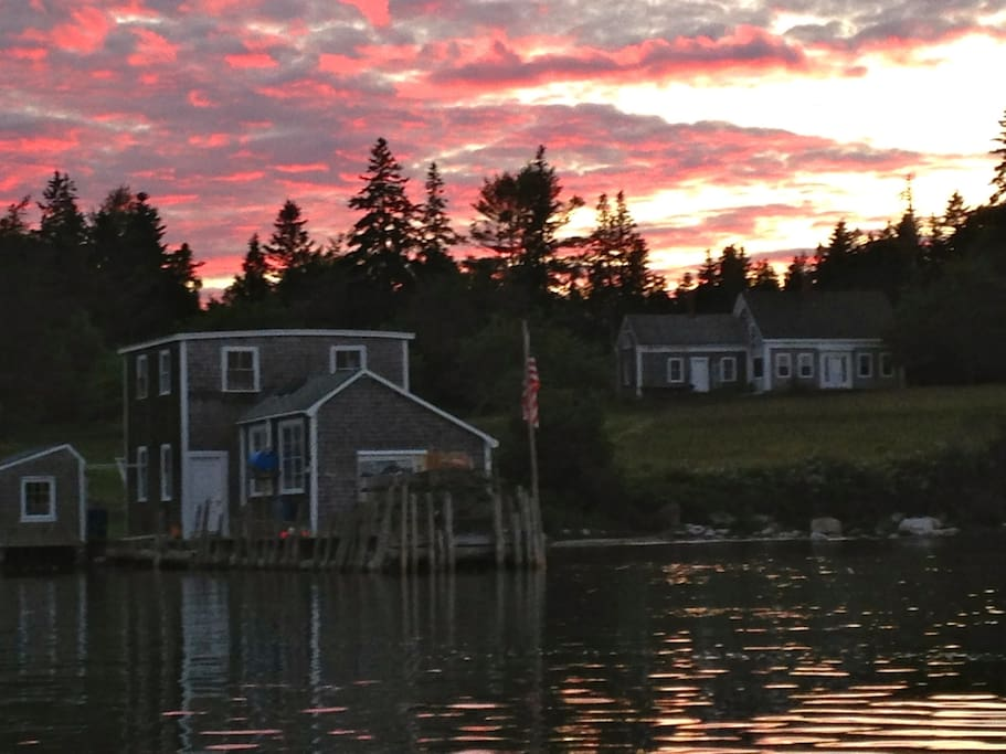 Sunset view from the water: wharf, Shop, and house up on the hill.