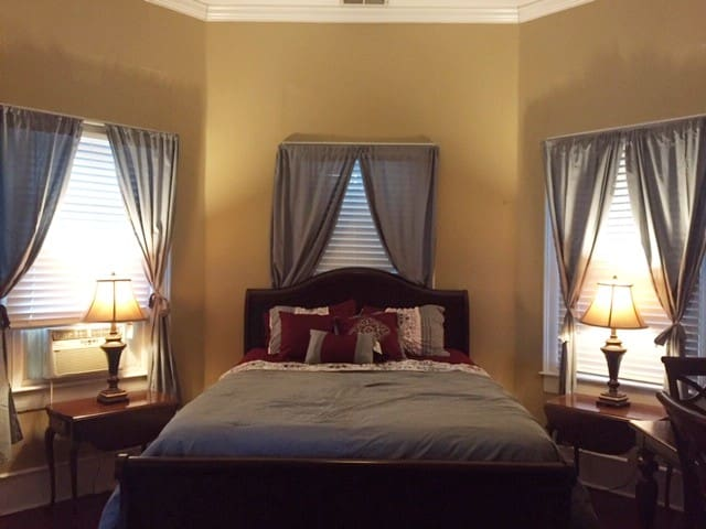 Cherry queen-sized bed with side tables and lamps.